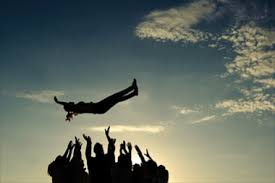 Image of a team tossing a team member in the air.